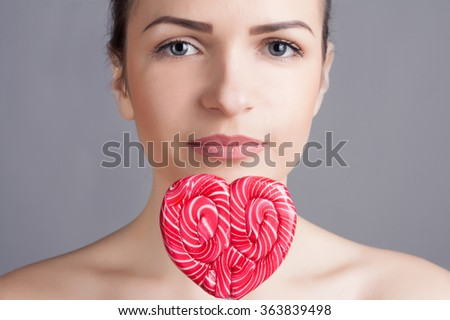 valentine's day concept. Close-up portrait of an young beautiful girl with lollipop in a shape of a heart. - stock photo