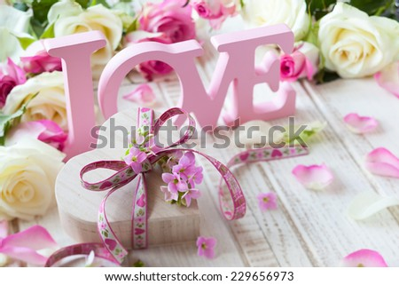 "Valentine's day concept with gift box, letters ""love"" and flowers on old vintage wooden background"