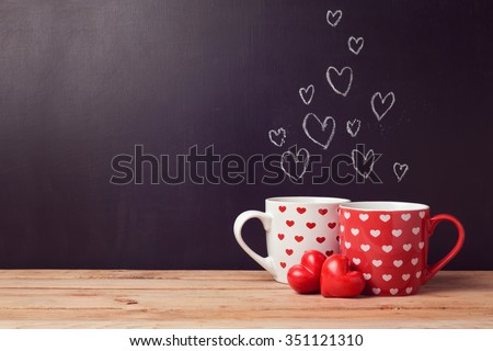 Valentine's day concept with hearts and cups over chalkboard background - stock photo