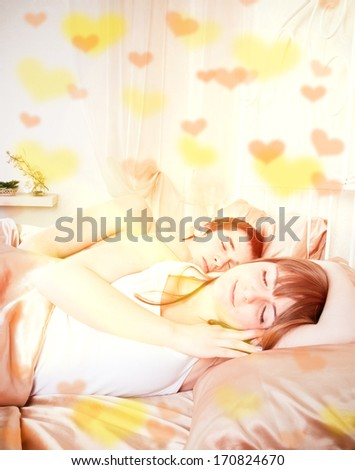 Valentine's day concept. Young couple sleeping in a bed - stock photo