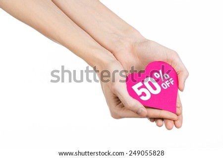 Valentine's Day discounts topic: Hand holding a card in the form of a pink heart with a discount of 50% on an isolated white background in studio - stock photo