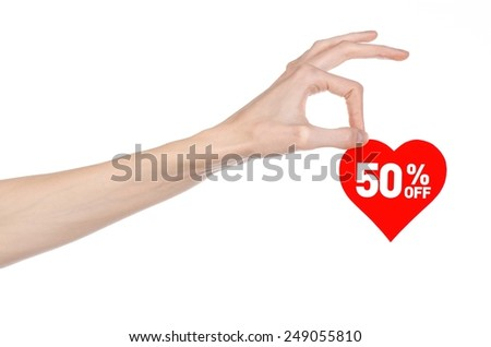 Valentine's Day discounts topic: Hand holding a card in the form of a red heart with a discount of 50% on an isolated white background in studio - stock photo