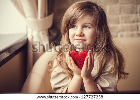 Valentine's Day -  dreaming cute child with red Heart in hands. Series of photos