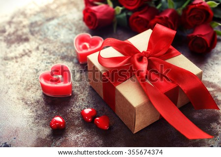 Valentine's Day, Gift box of kraft paper with a red ribbon and  candles. Rustic style - stock photo