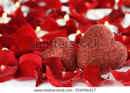 Valentine's Day hearts surrounded by rose petals and lite candles against a white background. Room for copy space with extreme shallow depth of field.