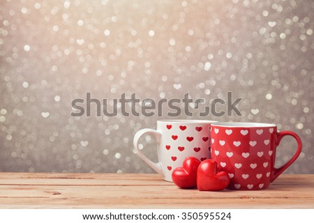 Valentine's day holiday celebration with hearts and cups over bokeh background - stock photo