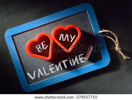Valentine's day invitation to be my Valentine. White chalk letters on blackboard background and two red hearts. - stock photo