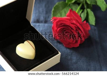 Ngày Valentine được Tổ chức kỷ niệm vào ngày 14. Đây là một lễ hội của tình yêu lãng mạn.  Sô cô la trái tim trong hộp đồ trang sức và bông hồng đỏ trên nền màu xanh sẫm.