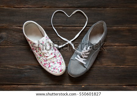 Valentine's Day love concept with grey and white with red flowers sneakers on a wooden floor background. Laces are in the form of heart. Concept of Love.