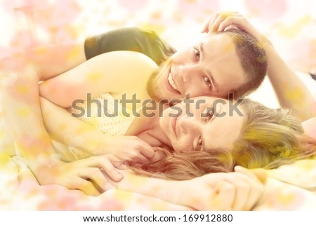 Valentine's Day. Lovely couple hugging on their bed at home - stock photo