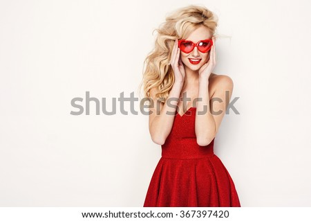 valentine's day portrait of an attractive young blonde girl with heart shaped glasses in red dress
