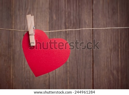 Valentine's Day, red paper heart hanging on the clothesline, wooden background - stock photo