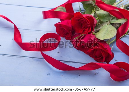 Valentine's Day: red roses and ribbons on rustic blue wooden background.
