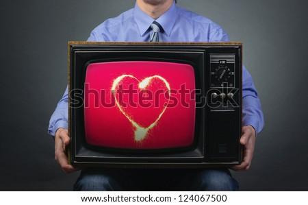 Valentine's Day. Retro TV featuring sparkling heart in the hands of men. - stock photo