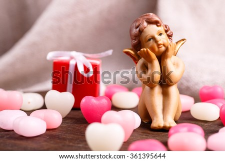 Valentine's day, Vintage angel porcelain sitting with a pink heart. - stock photo
