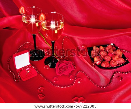 Valentine's Day. Wedding ring and glasses of champagne with strawberry, red roses and ornaments on black background. Red black still life.