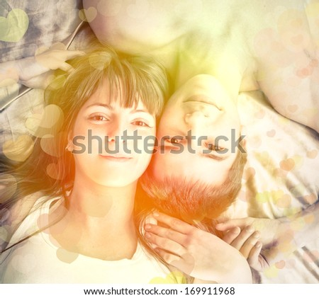 Valentine's Day. Young happy couple in bed  - stock photo