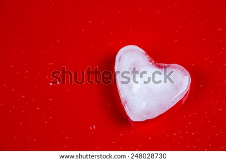 Valentine's greeting card with ice heart and bubbles on red background - stock photo