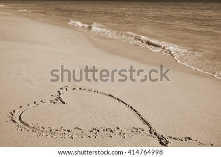 Valentine's love heart on the beach sand in sepia. Honeymoon vacations and Valentine's Day theme