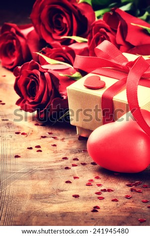 Valentine's setting with bouquet of red roses and present in box  - stock photo
