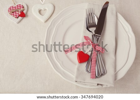 Valentine table setting with heart ornaments, copy space background, selective focus, vintage tone - stock photo