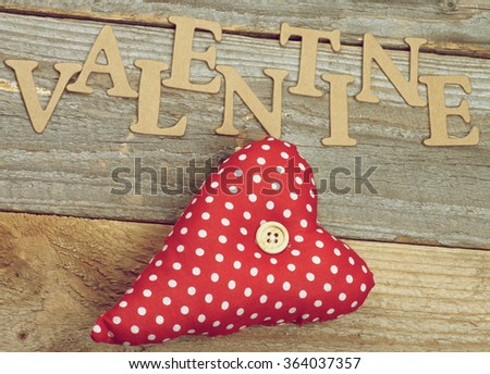 Valentine Theme Background with Cardboard Words and Handmade Textile Red Polka Dot Heart closeup on Rustic Wooden background