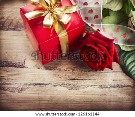 Valentine. Valentines Rose Flower and Gift Box over Wooden Background. Red Valentine's Day Border Art Design on Wood - stock photo
