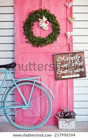Valentine wreath and sign board on wooden vintage pink door - stock photo