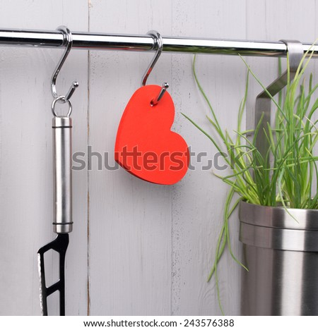 Valentines and mothers day background. Red heart and kitchen cooking utensil hanging on stainless steel rack. Cheese knife and bucket with green onion. Rustic gray wooden wall. Copy space - stock photo