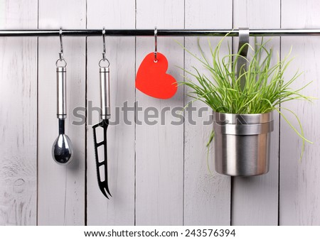 Valentines and mothers day background. Red heart and kitchen cooking utensil hanging on stainless steel rack. Cheese knife, ice cream scooper and bucket with green onion. Rustic gray wooden wall. - stock photo