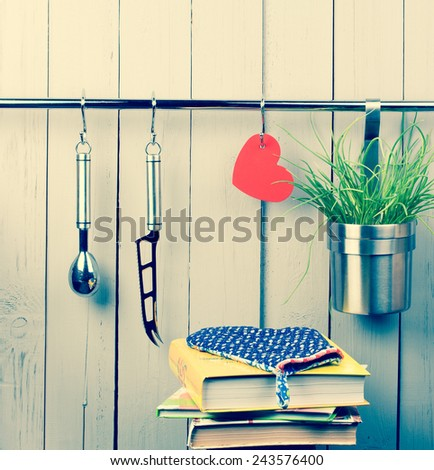 Valentines and mothers day background. Red heart and kitchen cooking utensil hanging on stainless steel rack. Cheese knife, ice cream scooper and bucket with green onion. Pot-holder on the top of pile - stock photo