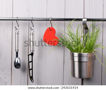 Valentines and mothers day background. Red heart and kitchen cooking utensil hanging on stainless steel rack. Cheese knife, ice cream scooper and bucket with green onion. Rustic gray wooden wall. Copy - stock photo