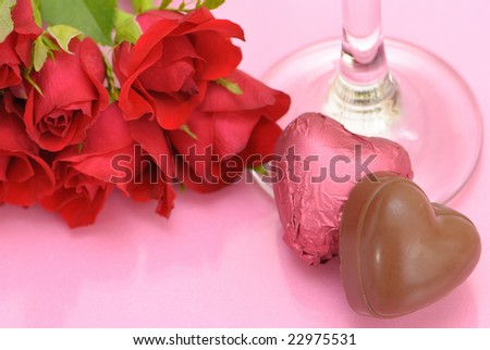 Valentines chocolates and roses with the stem of a champagne glass