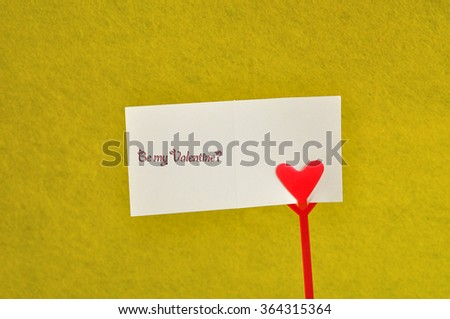Valentines day. A note holder with a red heart with a note reading be my valentine isolated against a yellow background - stock photo