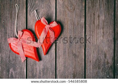 Valentines day background. Couple of red hearts with checkered ribbon on wooden background. Top view