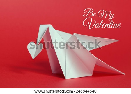 valentines day background. Origami dove carrying paper heart with her beak. - stock photo