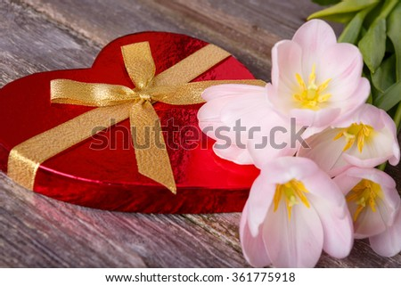 Valentines Day background - red heart with ribbon bow and flowers tulips on wooden background.