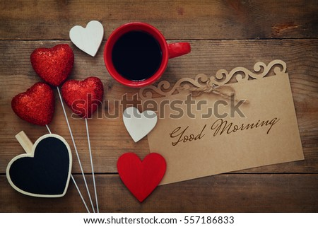 Valentines day background. Red hearts and cup of coffee on wooden background. Flat lay composition