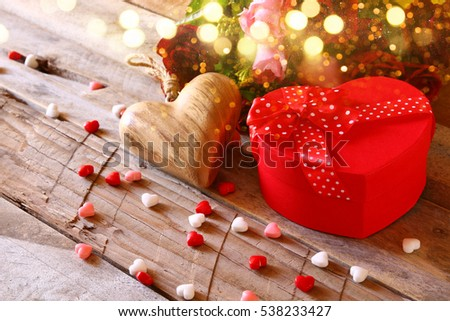 Valentines day background. Red hearts and present box on wooden table. Glitter overlay