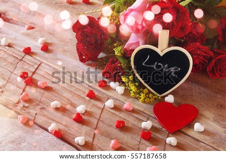 Valentines day background. Red hearts and roses on wooden table. Filtered and toned image. Glitter overlay