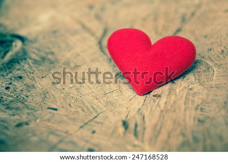 Valentines Day background with Fabric red heart cut on wood trunk. Retro filter. - stock photo