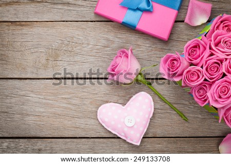 Valentines day background with gift box full of pink roses and handmaded toy heart over wooden table. Top view with copy space - stock photo