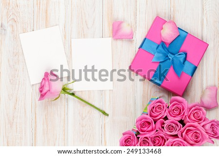 Valentines day background with gift box full of pink roses and two blank photo frames over wooden table. Top view with copy space - stock photo