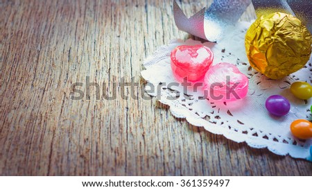 Valentines day background with pink hearts and color chocolate on hearts paper
