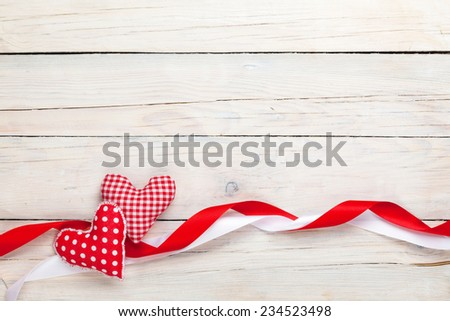 Valentines day background with toy hearts and ribbons over white wooden table background - stock photo