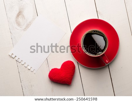 Valentines day blank greeting card, coffee cup and heart shaped toy over white wooden table - stock photo