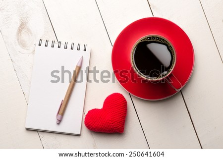 Valentines day blank notes with pen, coffee cup and heart shaped toy over white wooden table - stock photo