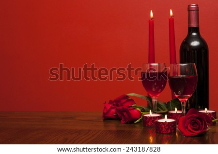 Valentines day: bottle of vine, glasses, red roses and candles a romantic time  - stock photo
