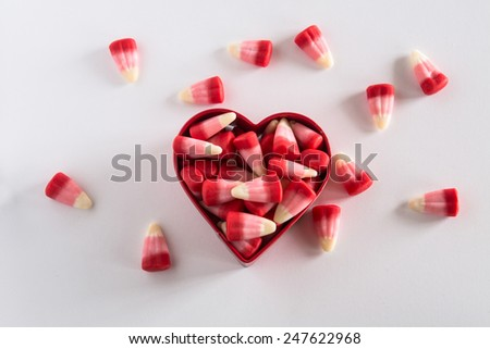 Valentines Day candy corn in heart shaped cookie cutter with candy scattered - stock photo