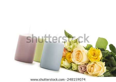 Valentines Day card background with three candles in pastel colors alongside a bouquet of fragrant fresh yellow and green roses symbolic of love over white with copyspace for your greeting - stock photo